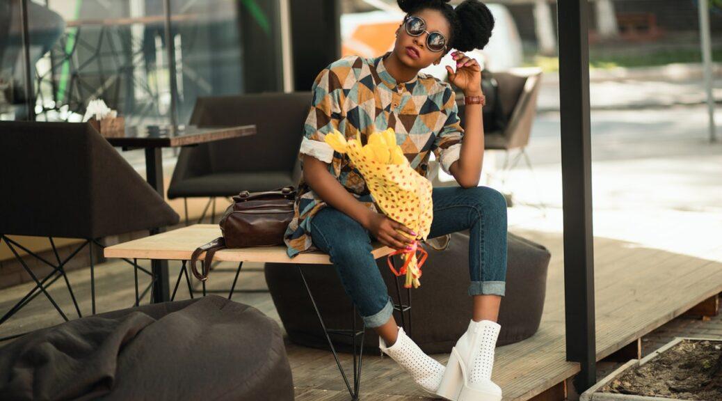 Dame i farverig skjorte sidder på cafe i udlandet